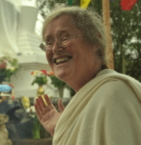 Lama Shenpen pointing at stupa